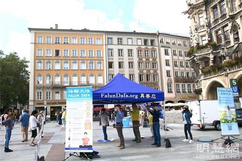 '图1:二零二一年九月一日,法轮功学员在德国慕尼黑玛琳广场(Marienplatz)举办真相日活动,图为法轮功学员展示功法。'