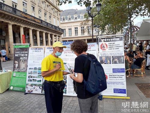 '图2~3:巴黎民众在征签表上签字,支持法轮功反迫害。'