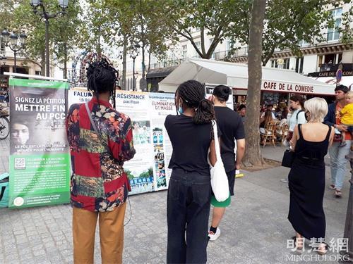 '图4:巴黎民众在柯莱特广场观看展板,了解法轮功真相。'
