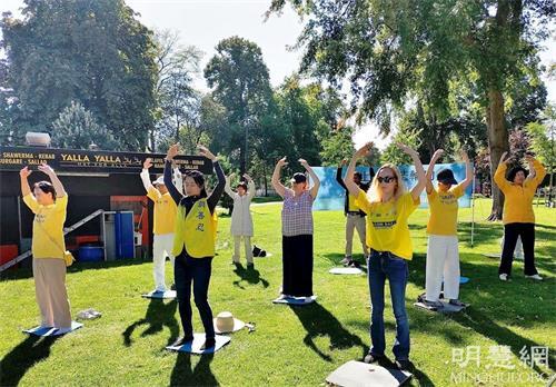 """'图1:二零二一年八月三十一日,瑞典法轮功学员在延雪平市的市政厅公园(JönköpingRådhusparken)举办了真相日活动。图为学员们在展示第二套功法""""法轮桩法""""。'"""
